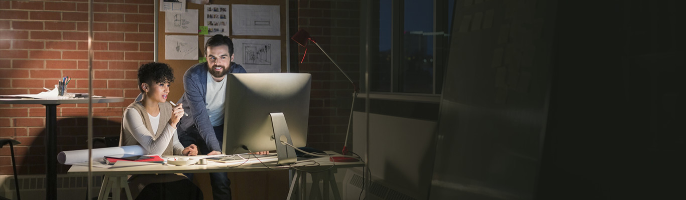 Two professionals looking at a computer screen in a loft office.