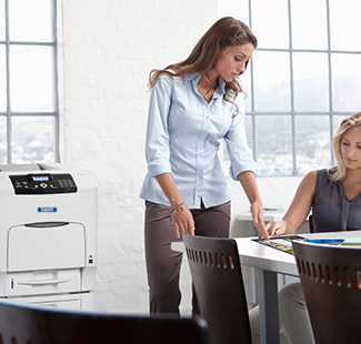 Woman standing at desk with Savin printer in background
