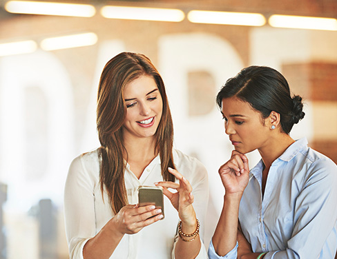 Two women looking at mobile phone