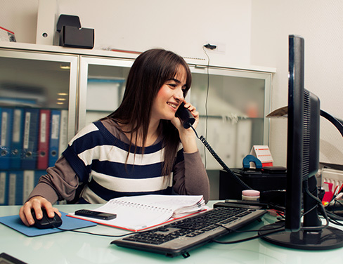 Woman in desk talking on the phone and using desktop computer.