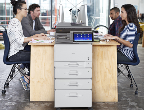Shared office of four employees using printer.