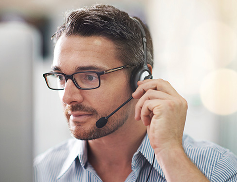 Close up of man with glasses on headset for customer service