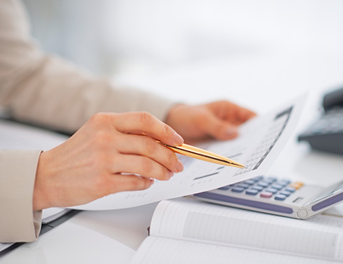 Close up of woman pointing at paperwork with pen and calculator in background