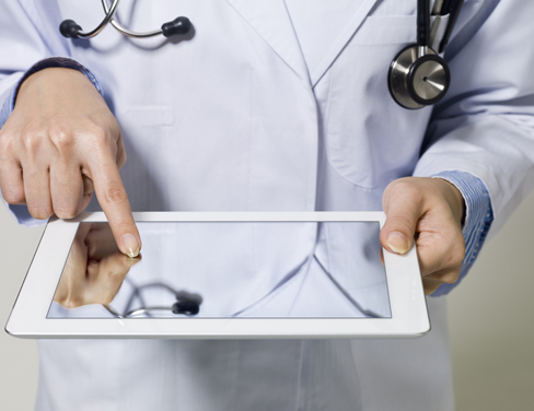 Photo of hands of a doctor touching a tablet