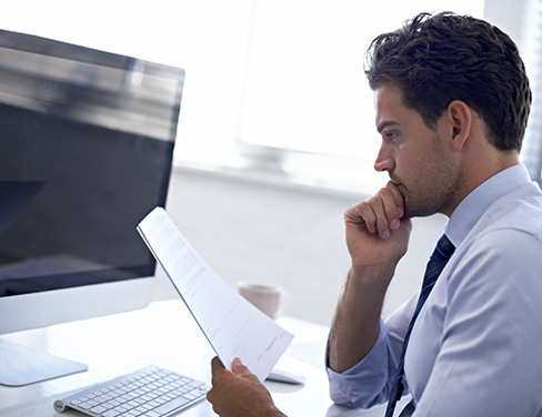 Man at desk with computer and paper