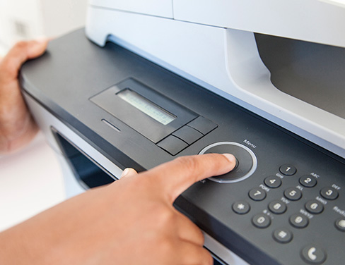 Close up of hands operating printer.