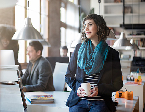 Woman standing and pondering in an open workspace