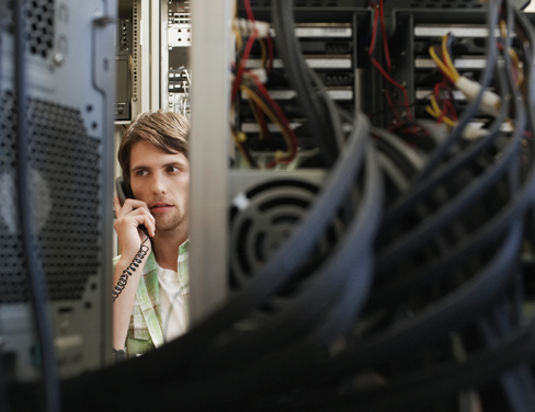 IT worker on his phone in a server room