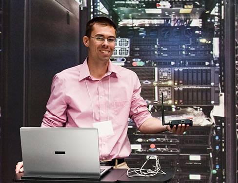 Photo of a smiling developer behind a laptop in an operations room.