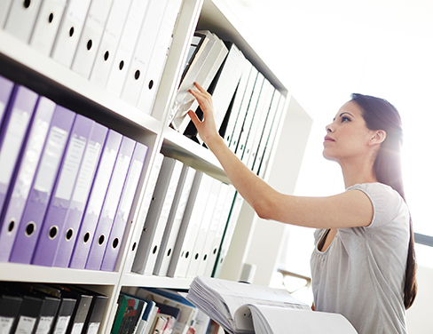 Woman looking at folders on a folder rack